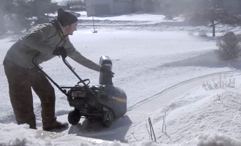 A person making adjustments to a snow blower.