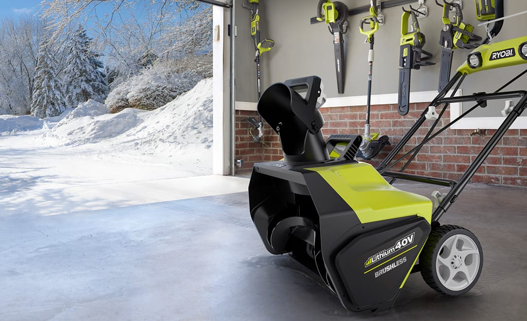 A battery powered snow blower stored in a garage.