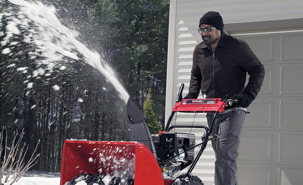 A person wearing safety goggles using a snow blower.