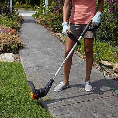 A woman uses a string trimmer to edge near her driveway.
