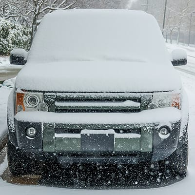 The front of a vehicle that is parked outside and covered in a couple inches of snow.