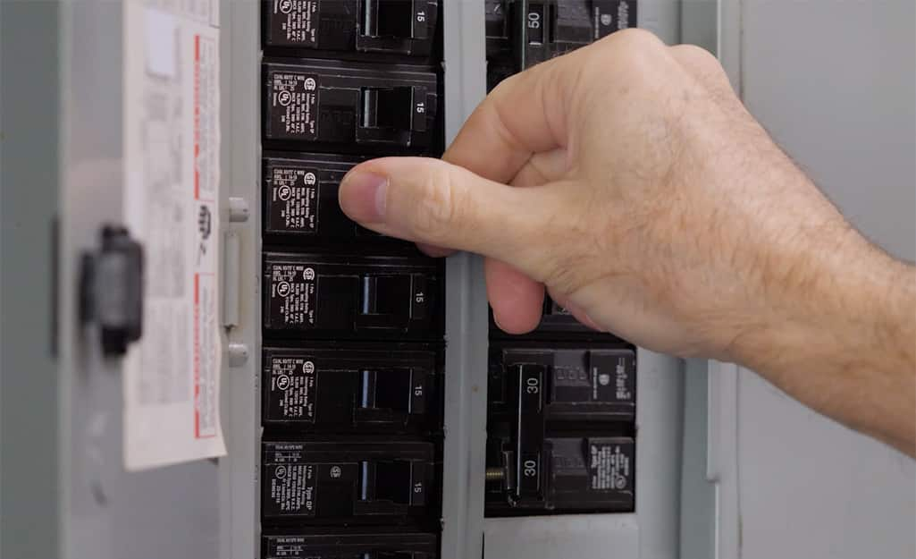 A person's hand turning off the circuit breaker.