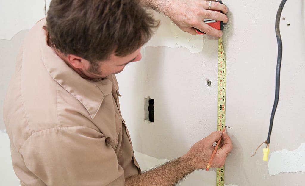 A person using a tape measure to mark for the outlet.