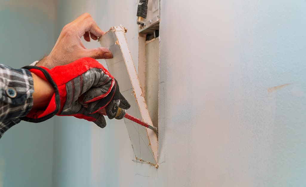 A person's hand pulling apart the cut wall.