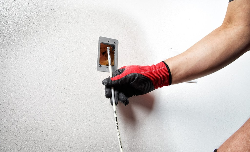 A person pulling the cable through the wall.