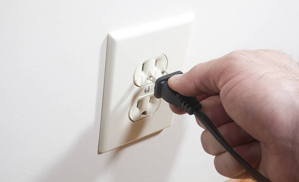 A person plugging a cord into an outlet.