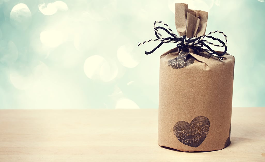 Brown paper wrapped around a cylindrical gift with ribbon tied to the top.