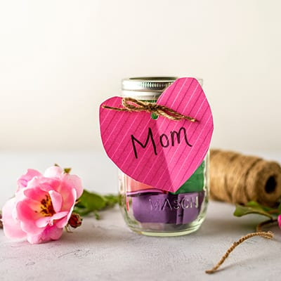 A jar with a pink heart tag tied to it.