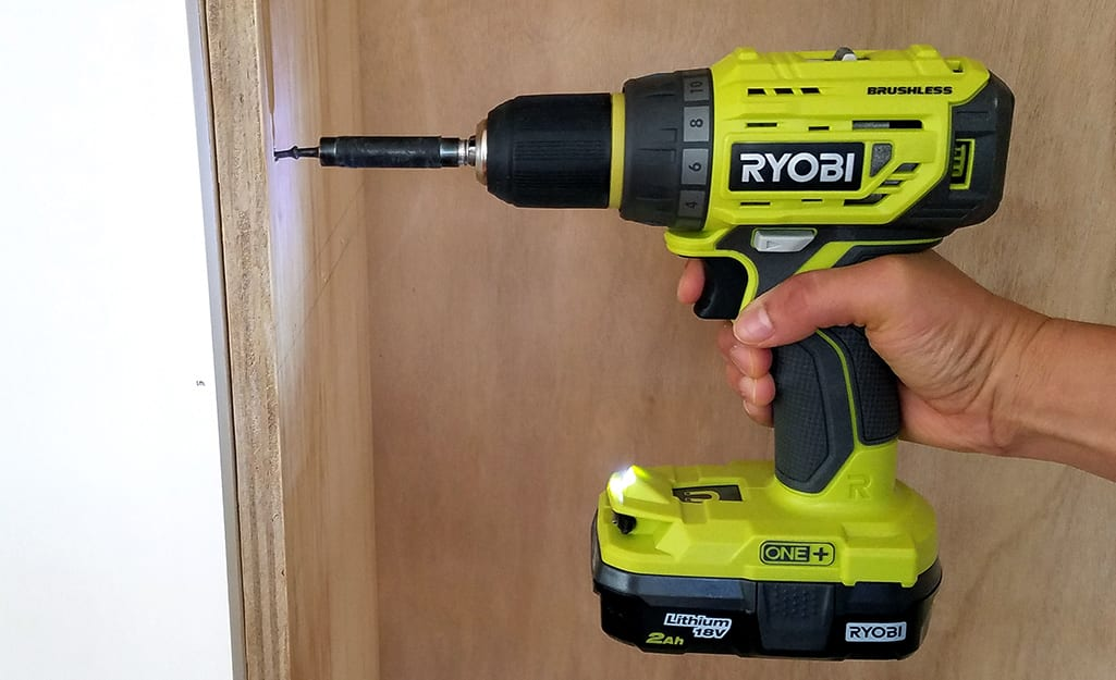 A person using a power drill to drill into a piece of wood against a wall.