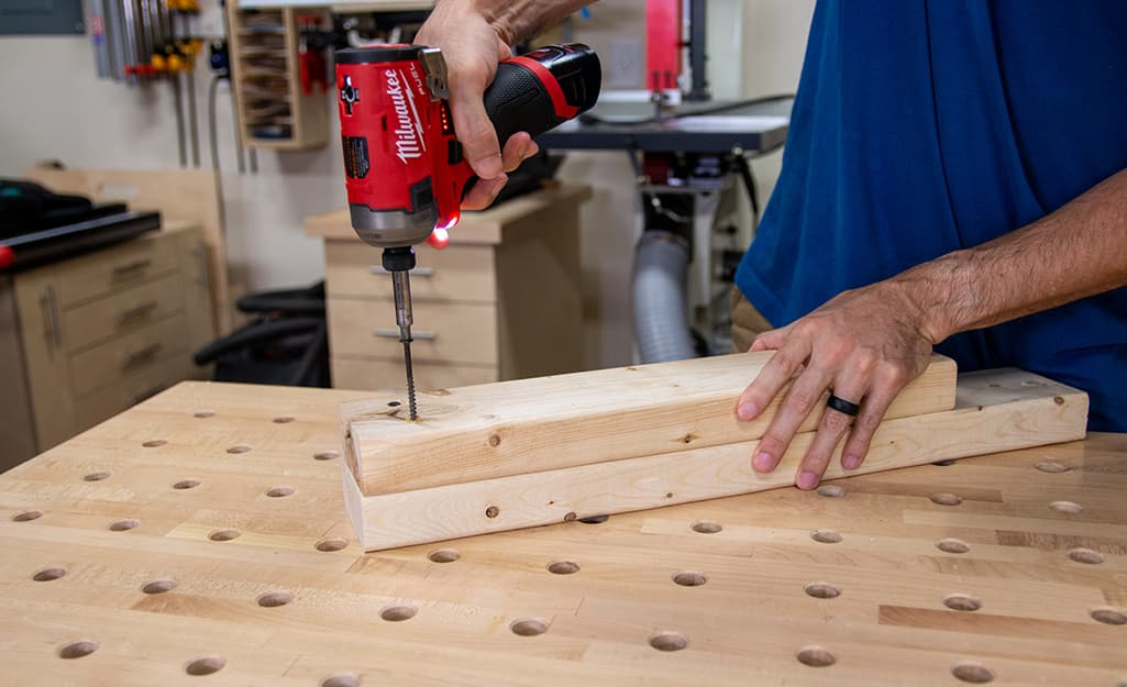 A person using an impact driver on two pieces of plywood.