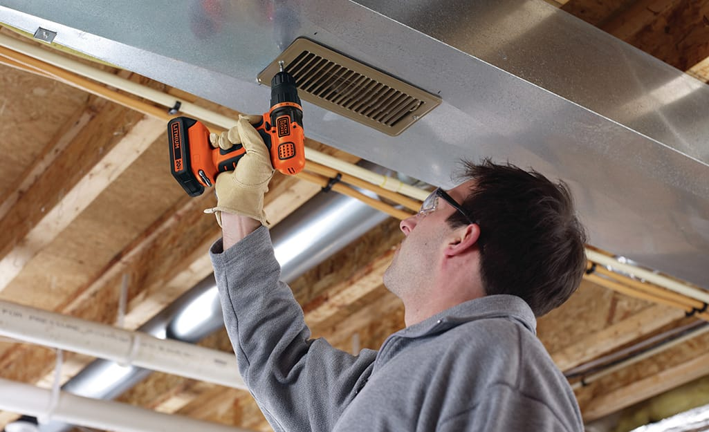 A man using a power drill on a large piece of wood.