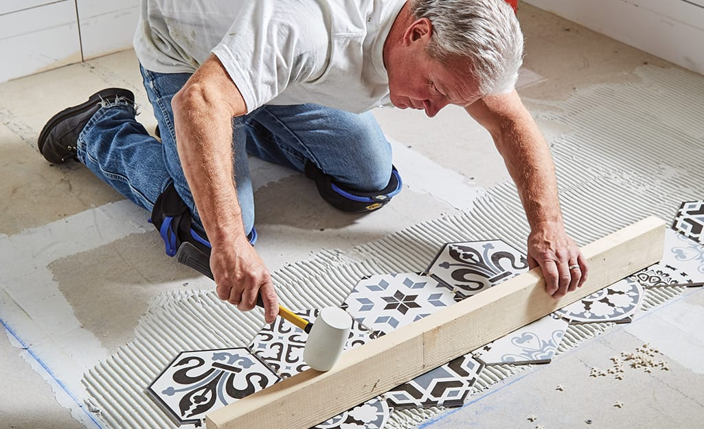 Man leveling rows of tile using a mallet and wood board.