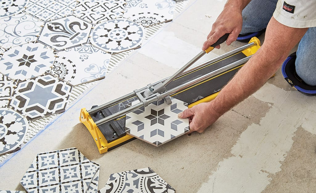 Man cutting tile with a manual tile cutter.