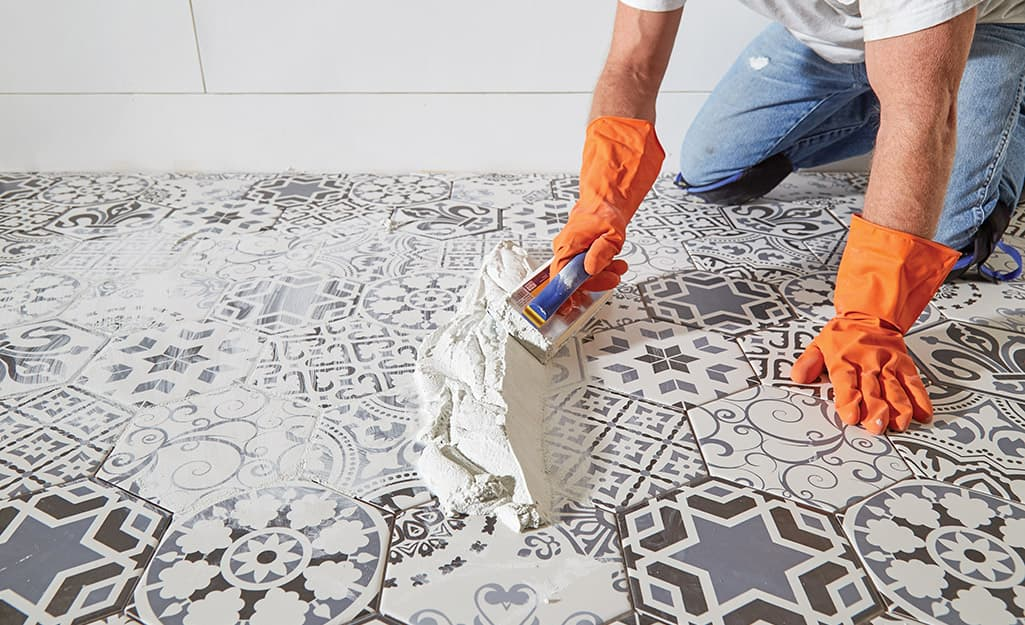 Someone grouting a blue and white tile floor.