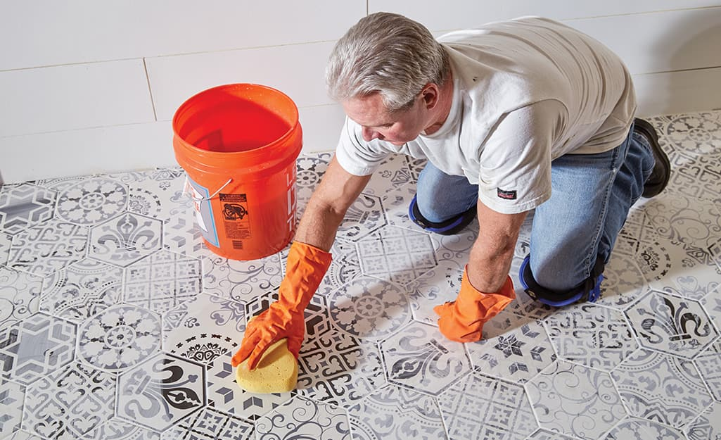 Person cleaning excess grout from tiles with sponge.