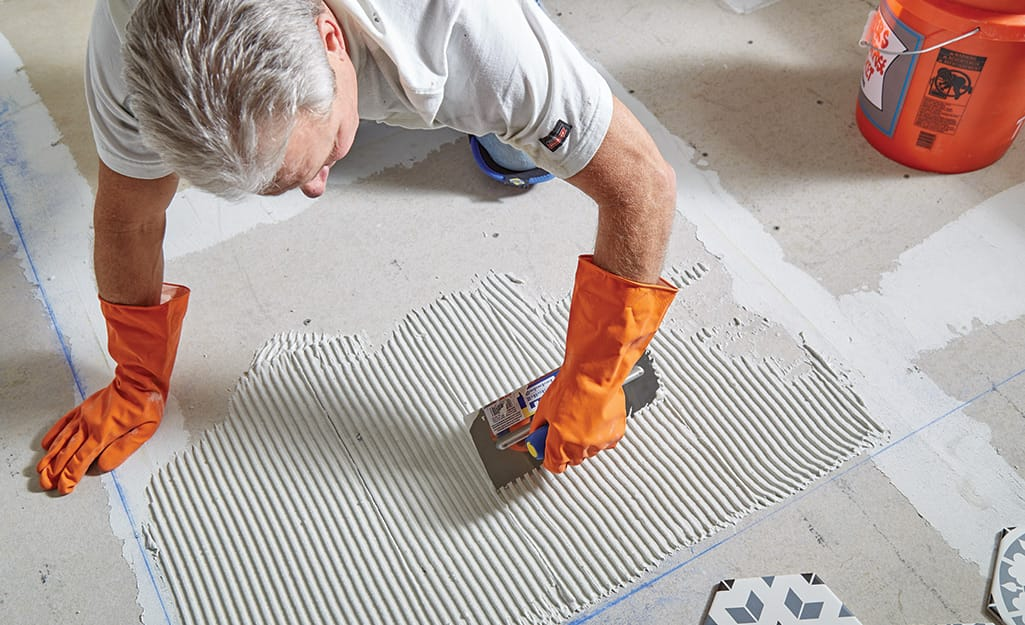Man smoothing thin-set with a trowel.
