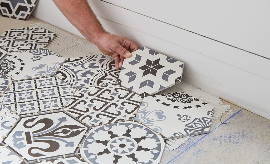 Person placing tile near a wall.