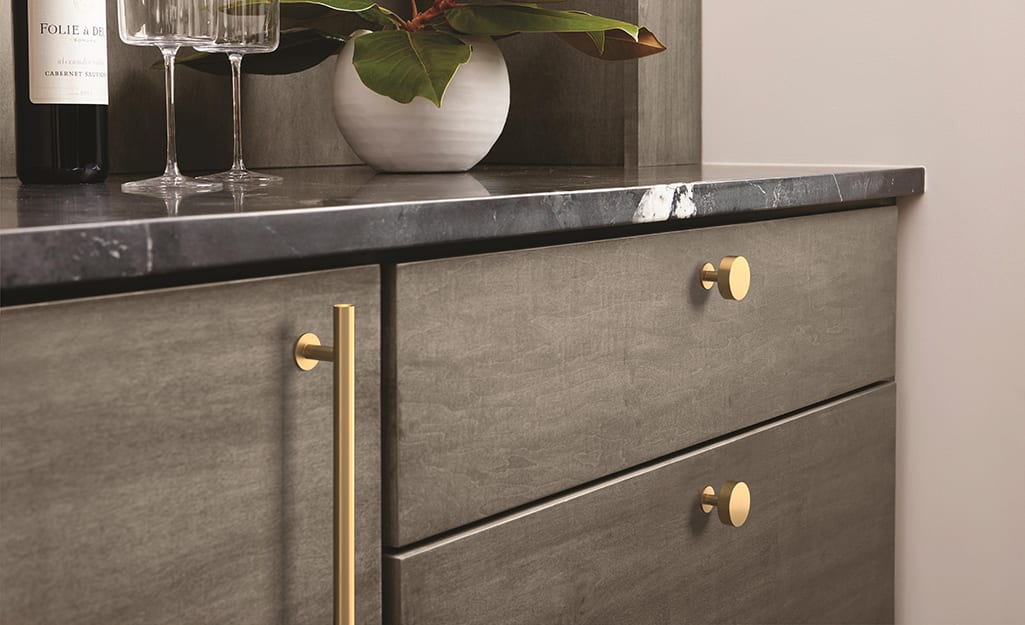 A kitchen cabinet with hardware that shows a refinished look.
