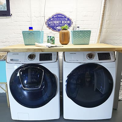 A white front load washer and dryer in a laundry room.