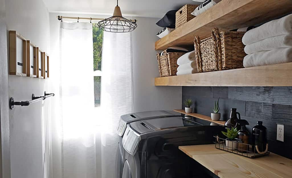 A laundry room with organized, wall-mounted wood shelves.