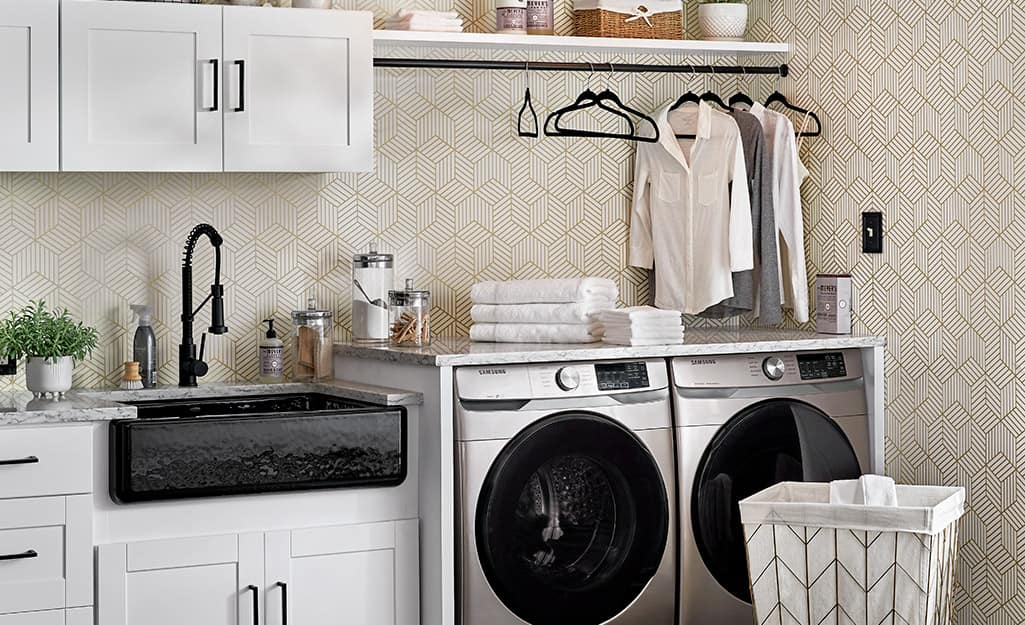 A laundry room with an apron sink, cabinets and a hanging bar above the washer and dryer.