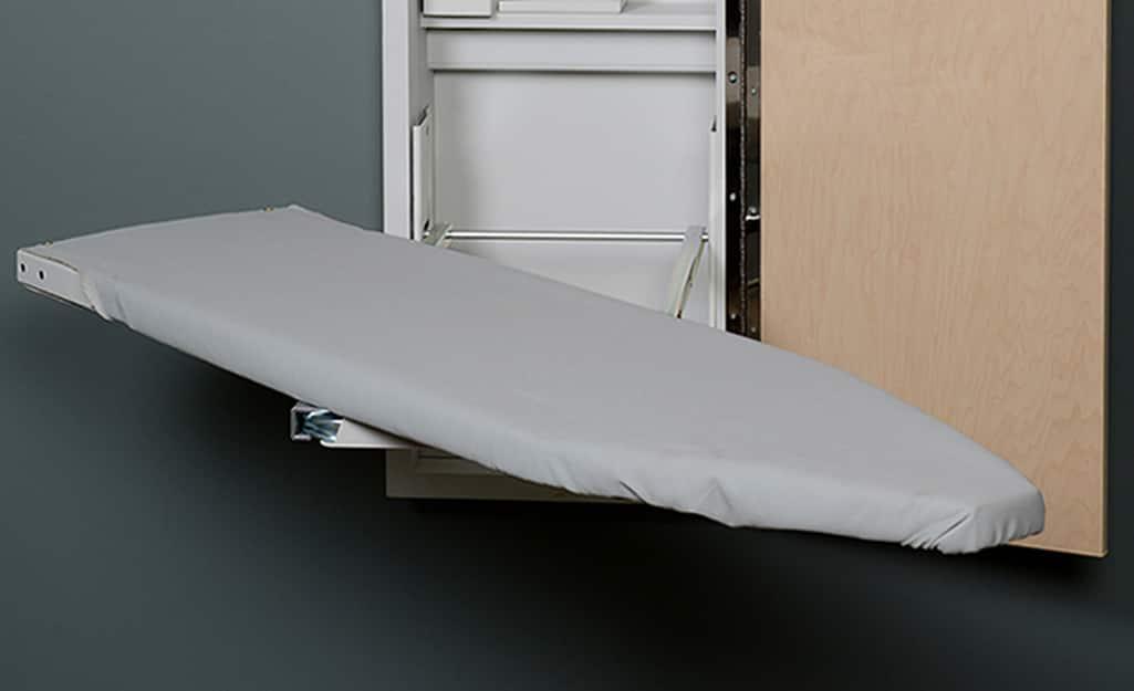 A fold-away ironing board mounted to a wall.