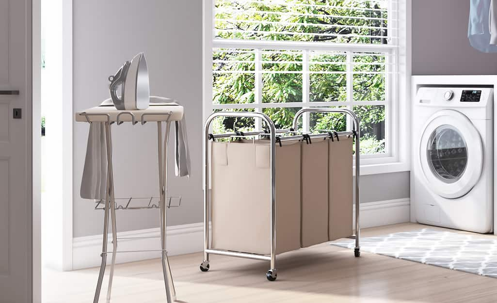 A laundry sorter and ironing board in a large laundry room.