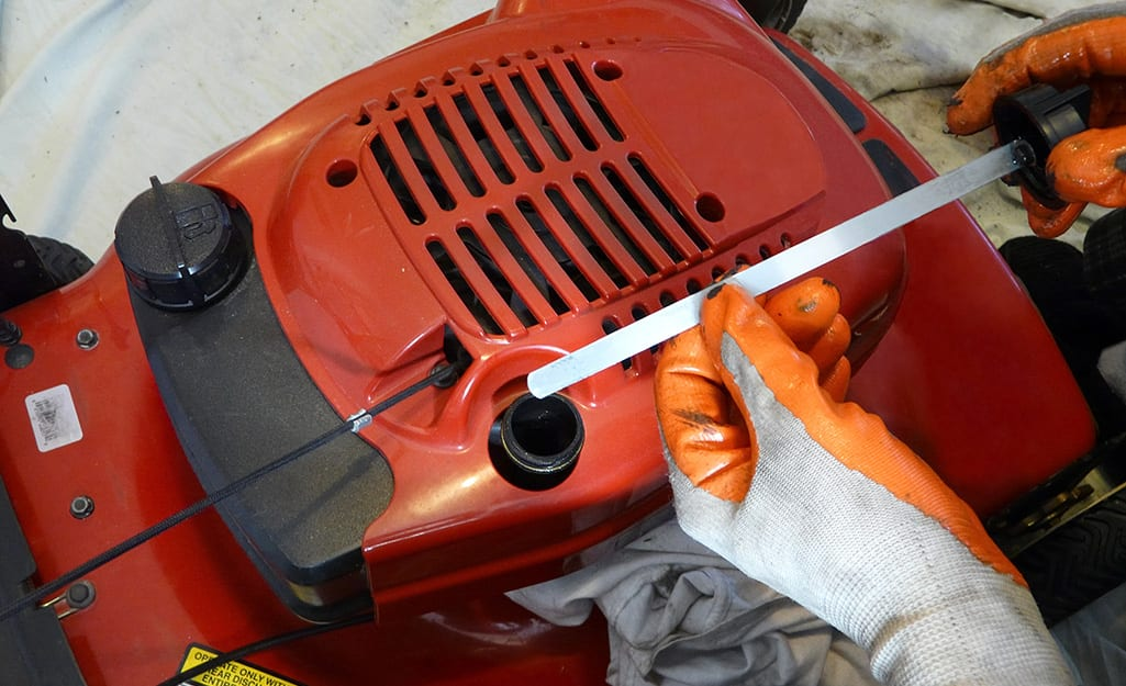 Someone changing oil in a lawn mower.