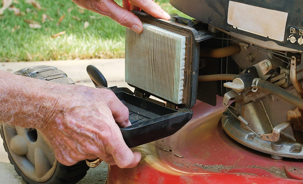 Someone changing the filter in a lawn mower.