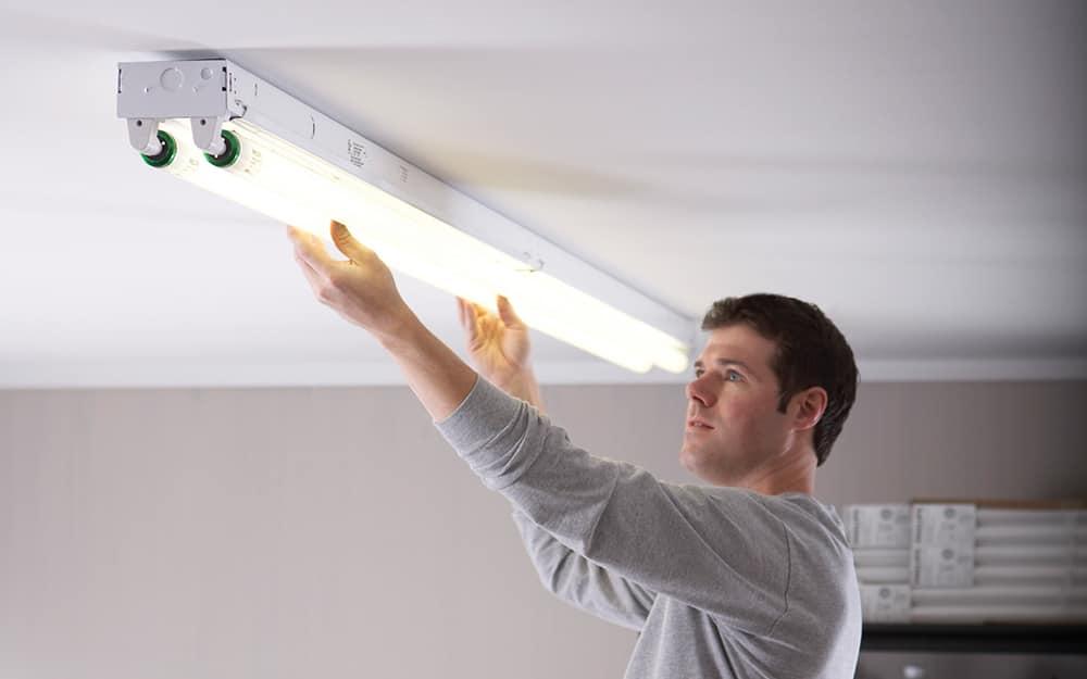 A man installing fluorescent tube lights.