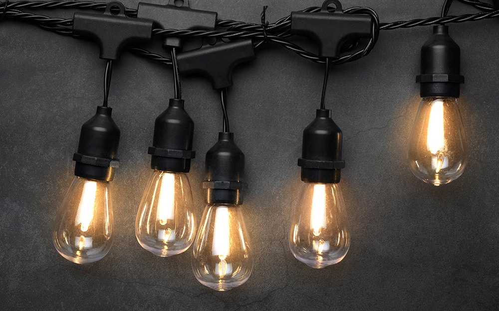 Edison-style LED bulbs hang on string lights.