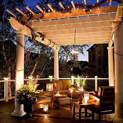 a residential deck illuminated by string lights and lanterns