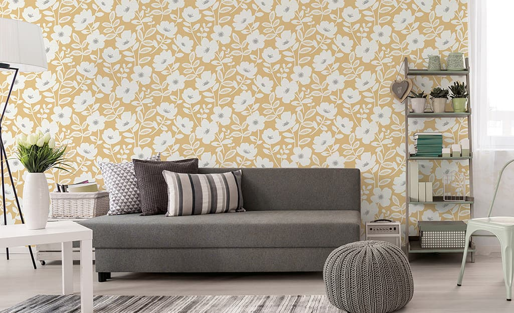 Yellow wallpaper in a living room with a grey sofa and other decor.