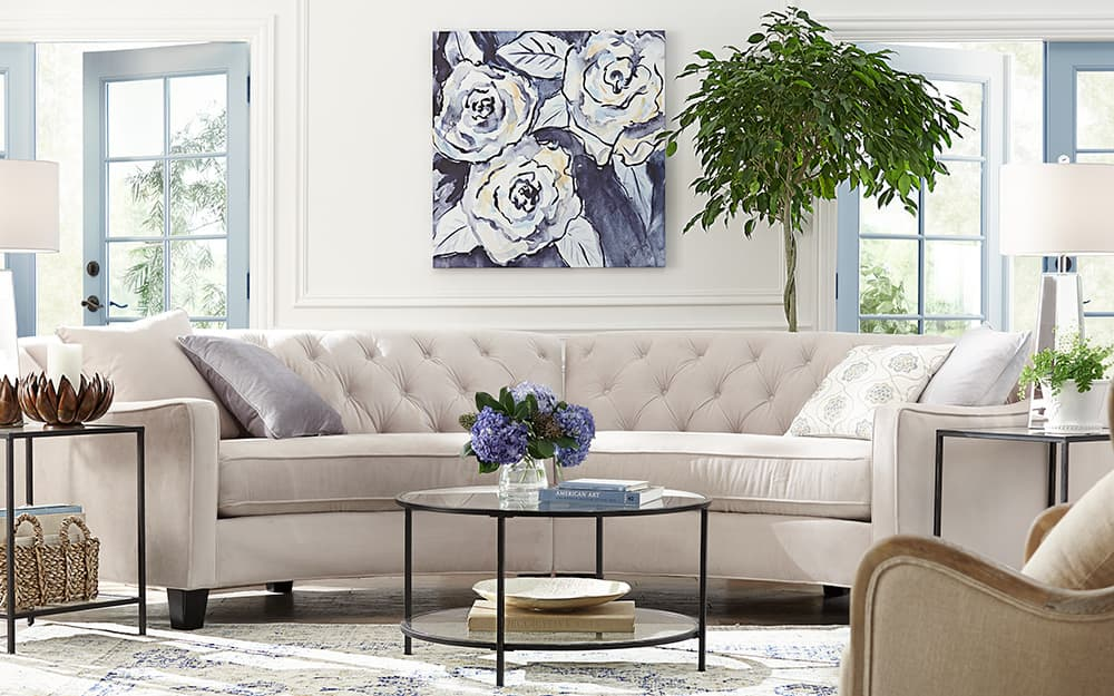 A living room with white sectional sofa and large framed art.