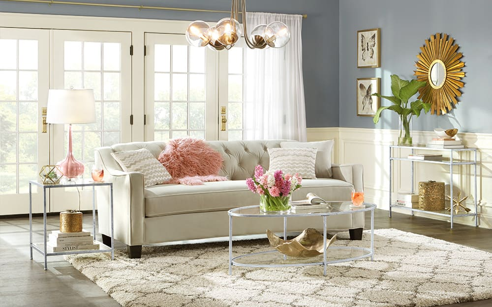 A living room with white sofa and area rug.