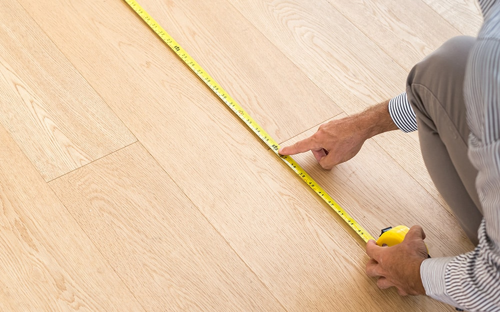 A person measuring part of the floor