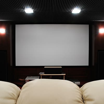 A home theater man cave with lounge chairs.