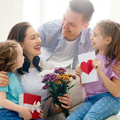 Woman surrounded by man and children giving her flowers and a card.