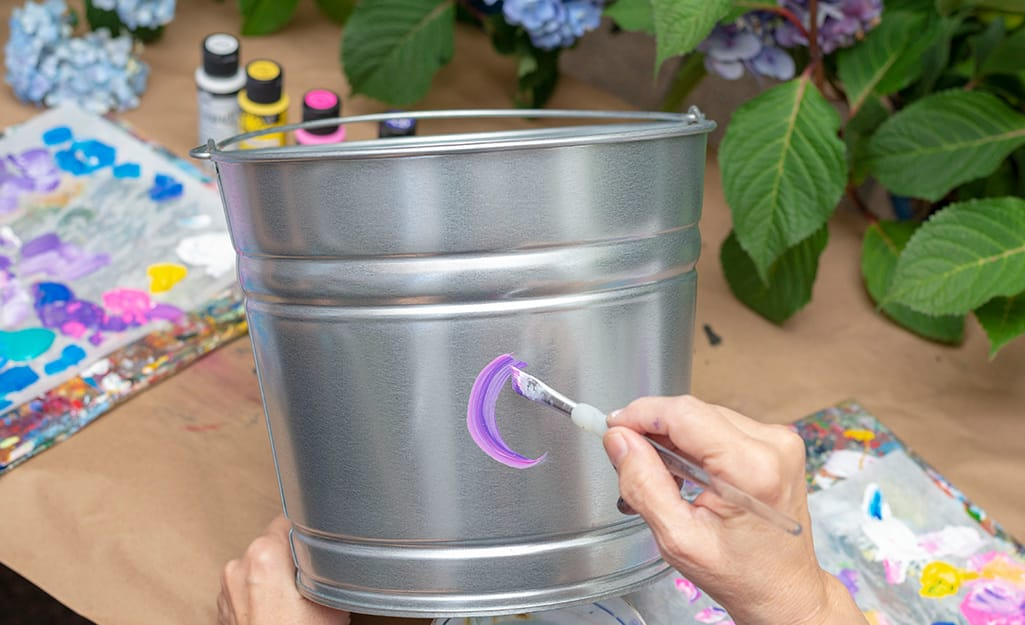 A person applying purple acrylic paint onto a galvanized bucket.