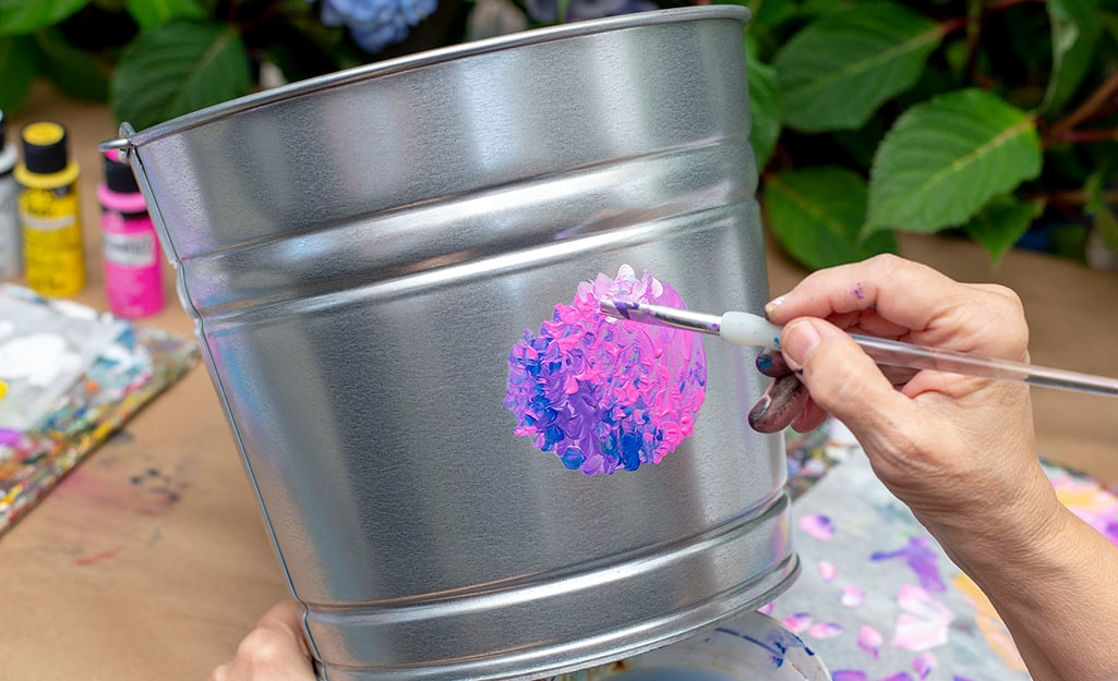 A person adding white paint to a galvanized bucket.