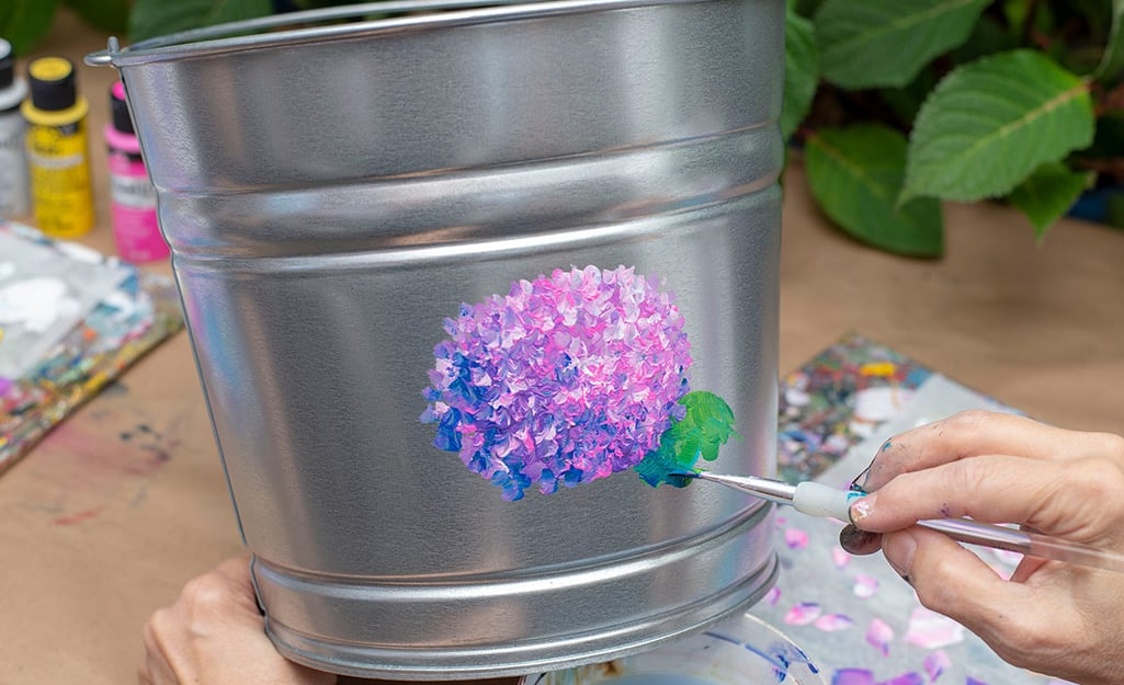 A person adding green paint to a galvanized bucket.
