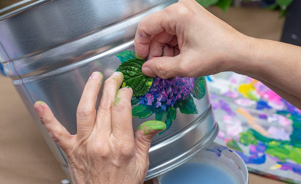 A person using a leaf to stamp paint onto a bucket.