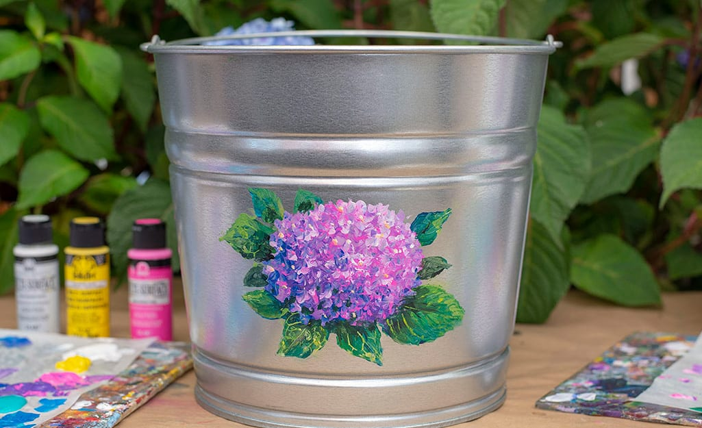 A galvanized bucket with a painted hydrangea on it.