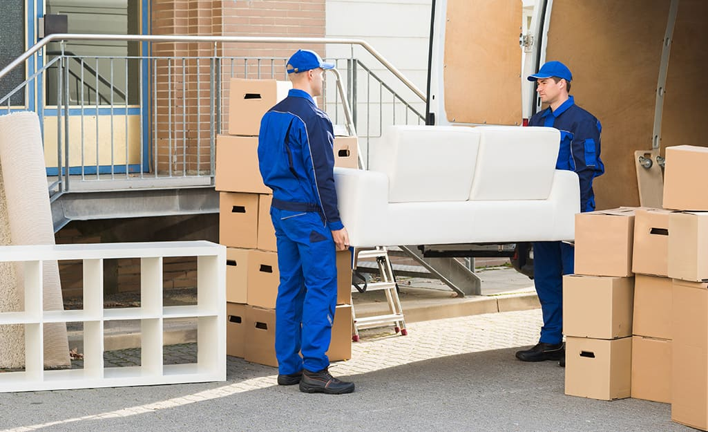 Professional movers load a sofa into a moving truck.