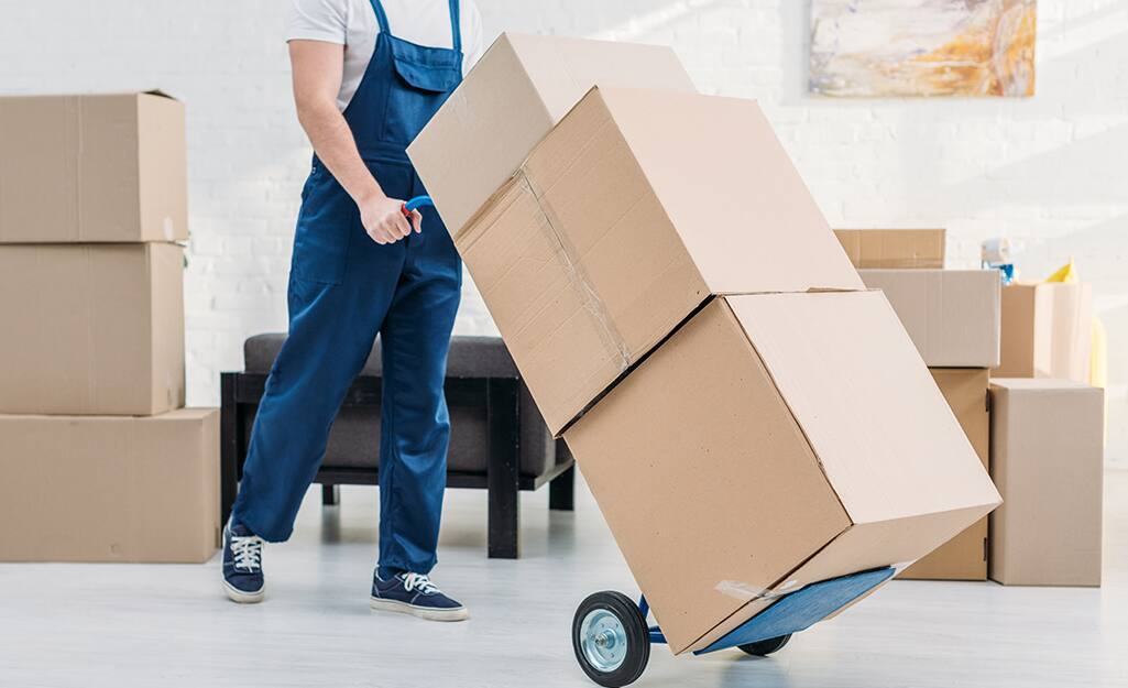 A man uses a dolly to carry three boxes.