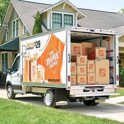 A moving truck loaded with boxes parked in a home's driveway.