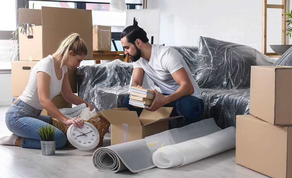Two people unpacking boxes in a living space.
