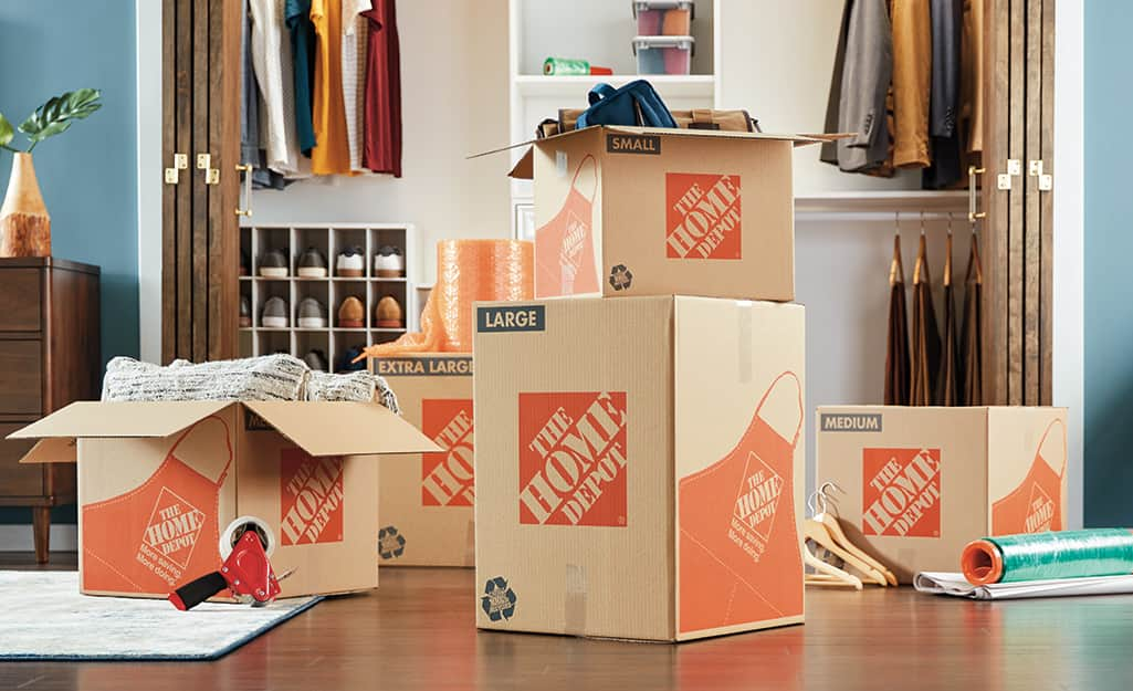 Several Home Depot moving boxes stacked in a closet.