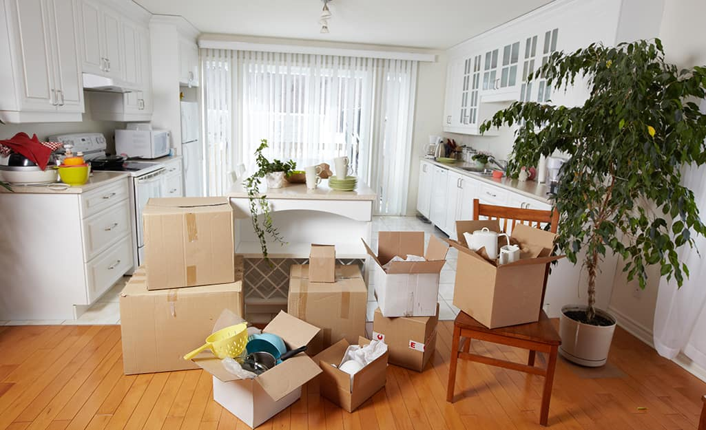A kitchen filled with different moving boxes.