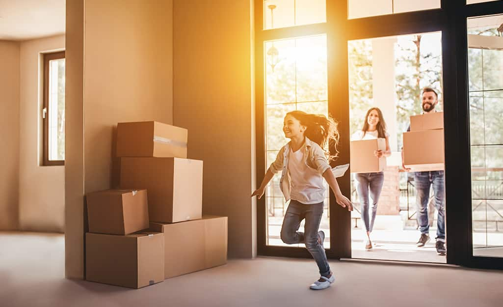 Girl running into new house full of moving boxes.